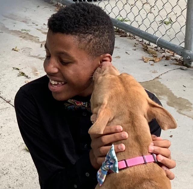 Darius Brown being licked on the face by a dog